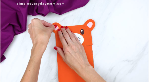 hands gluing pink inner ears to tiger craft