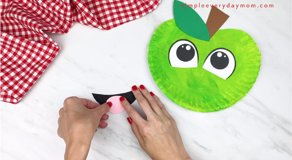 hands gluing paper tongue on paper mouth, with paper plate apple to the right