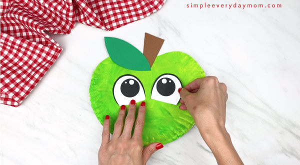 hands gluing on stem on paper eyes on paper plate apple