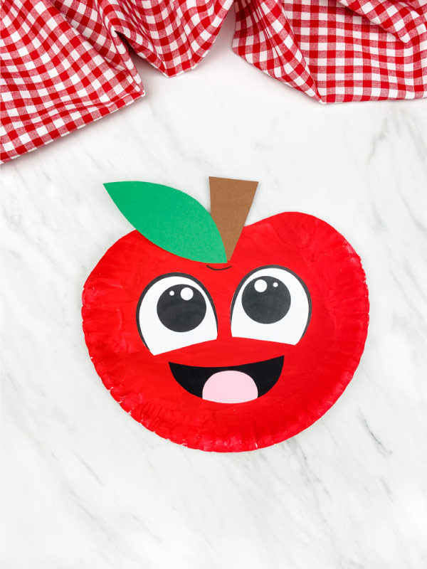 red paper plate apple craft on marble background with checkered fabric on top