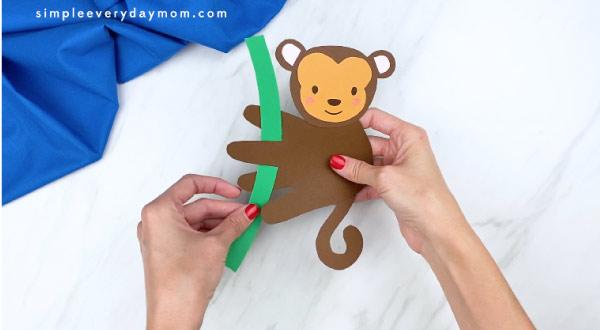 hands weaving green paper through monkey handprint arms