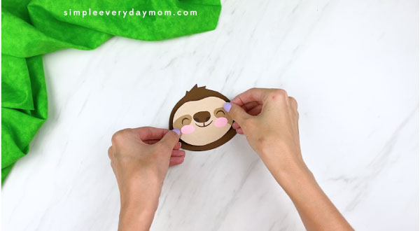 hands gluing sloth face to head