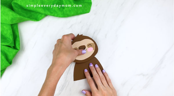 hands gluing sloth head onto body