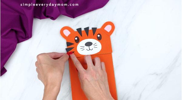 hands gluing tiger stripes to paper bag tiger face