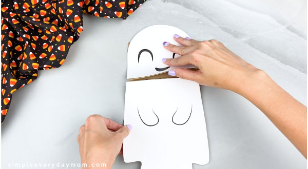 hands gluing ghost body onto paper bag