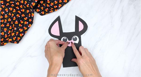 hand gluing nose onto paper bat craft