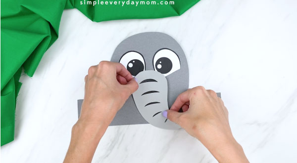 Hands gluing elephant trunk to paper elephant head
