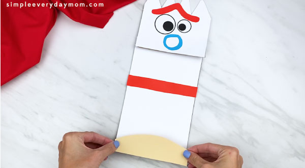 hands gluing forky clay base paper onto puppet craft