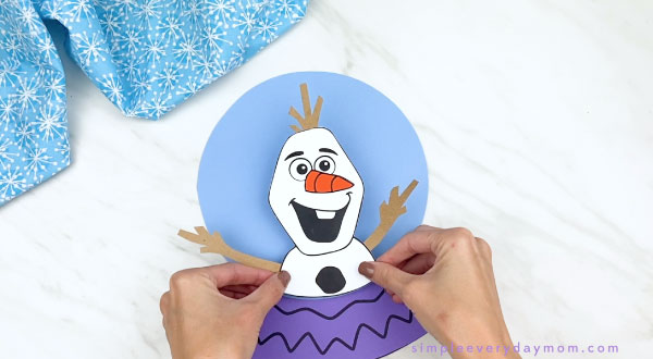 hands gluing olaf to paper snowglobe