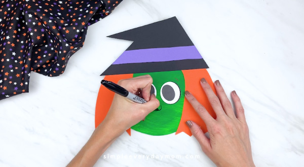 hands drawing on nose and mouth on paper plate witch