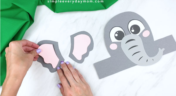 Hands gluing pink inner ear to gray outer ear of elephant craft