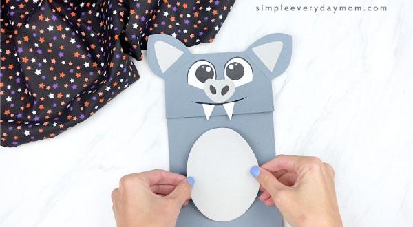 hands gluing belly onto paper bag bat craft