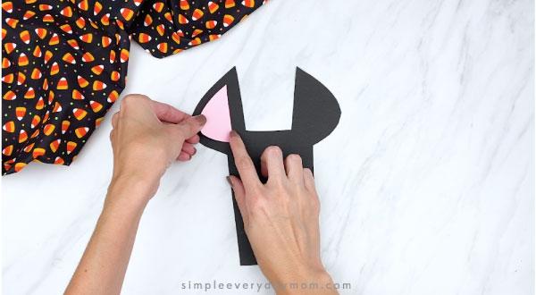 hands gluing pink inner ear to paper bat