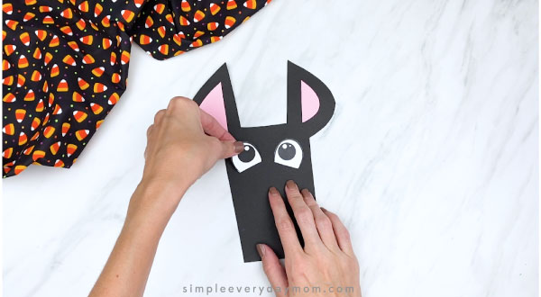 hands gluing eyes onto paper bat craft