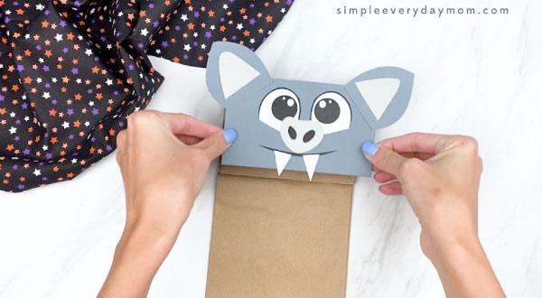 hands gluing paper bag bat face onto brown paper bag flap