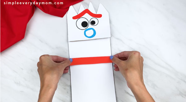 hands gluing arms onto forky paper bag puppet craft