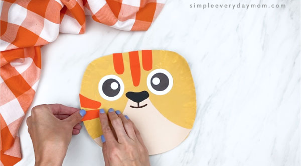 hands gluing orange stripes onto paper plate tabby cat craft