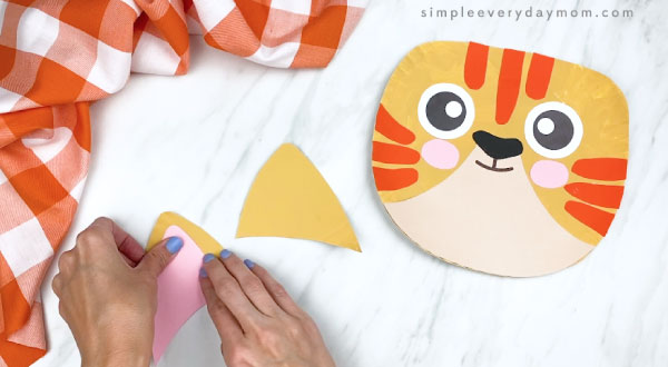 hands gluing pink inner ear to outer ear of paper plate craft