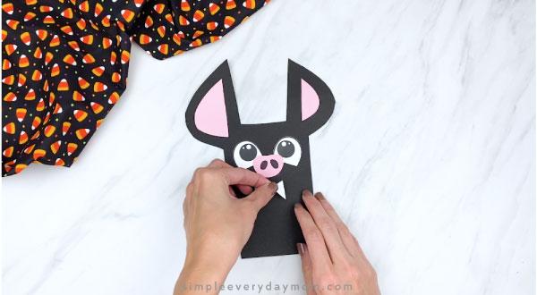 hands gluing fangs to paper bat craft