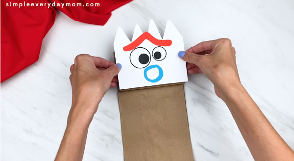 hands gluing forky face onto paper bag flap