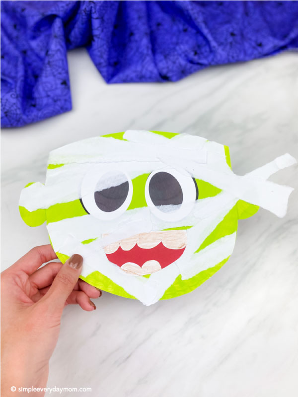 hand holding green paper plate mummy craft