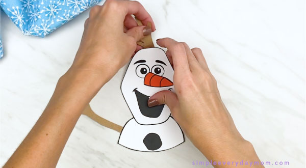 hands gluing stick hair to paper Olaf