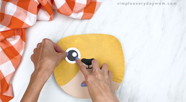 hands gluing eye onto paper plate cat craft