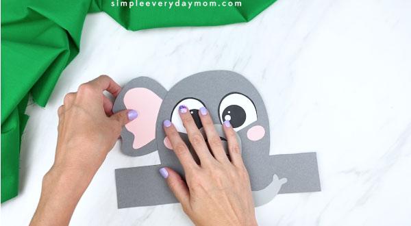 Hands gluing ears to elephant headband craft