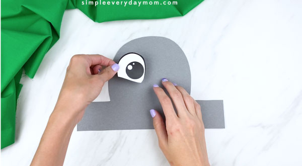 Hands gluing eye to elephant headband craft