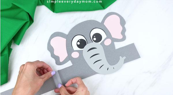 Hands taping headband extenders to elephant headband craft