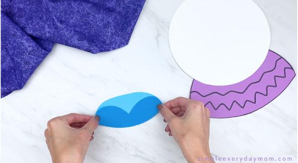 hands gluing paper Elsa dress together