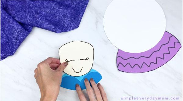 hands gluing paper Elsa head to body