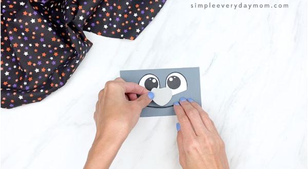 hands gluing nose onto paper bag bat face