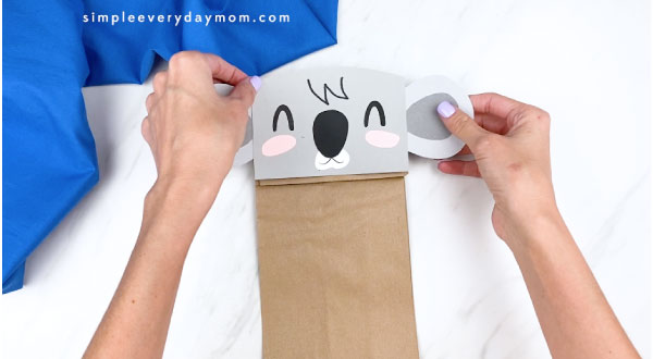 Hands gluing koala face to brown paper bag