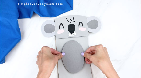 Hands gluing gray belly to paper bag koala craft