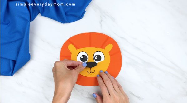 hands gluing nose onto paper lion face