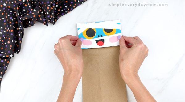 hands gluing mummy face onto paper bag flap