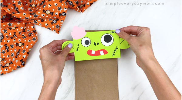 Hands gluing zombie head onto paper bag