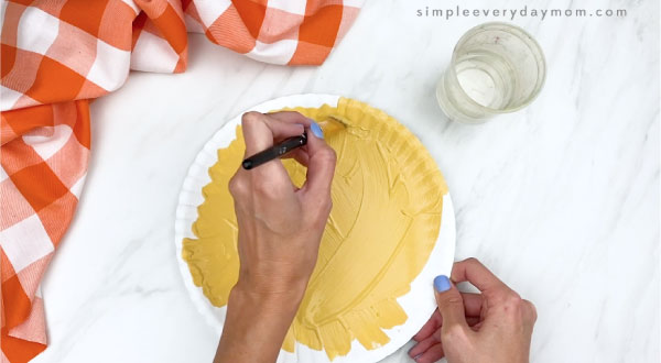 hand painting paper plate a muted yellow brown color