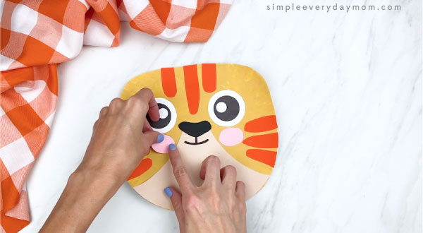 hands gluing cheeks onto paper plate cat craft