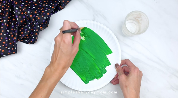 hands painting paper plate green
