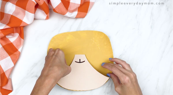 hands gluing mouth onto paper plate cat