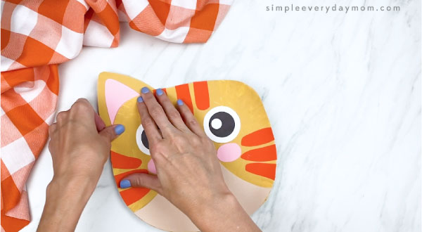 hands gluing ears to back of paper plate cat craft
