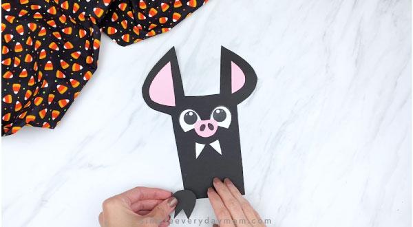 hands gluing feet to paper bat craft