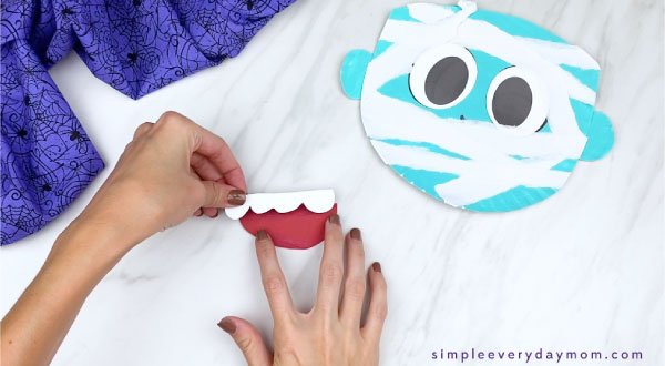 hands gluing teeth onto paper plate mummy mouth