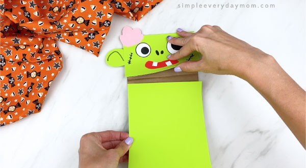 Hands gluing green body piece to zombie puppet craft