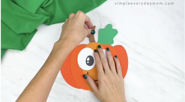 hands gluing stem to paper pumpkin craft