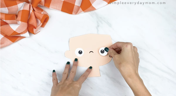 hands gluing eyes to paper face