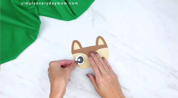 hands gluing eyes to paper squirrel head