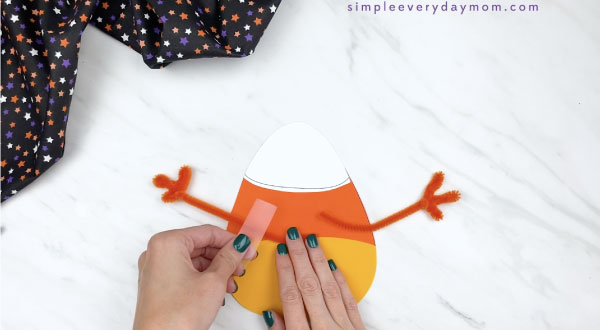 hands taping pipe cleaner arms to the back of paper candy corn craft